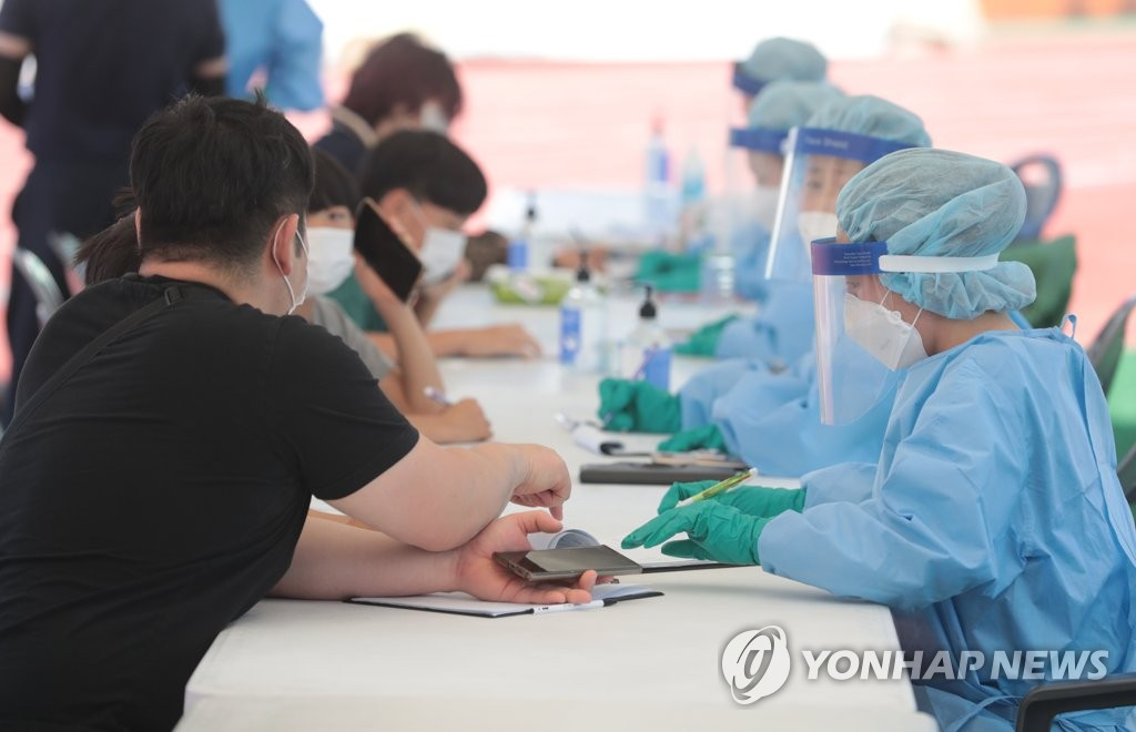 In the file photo taken July 17, 2020, people receive coronavirus tests at a stadium in the town of Hallim on South Korea's largest island of Jeju after four of its residents tested positive for COVID-19. (Yonhap)