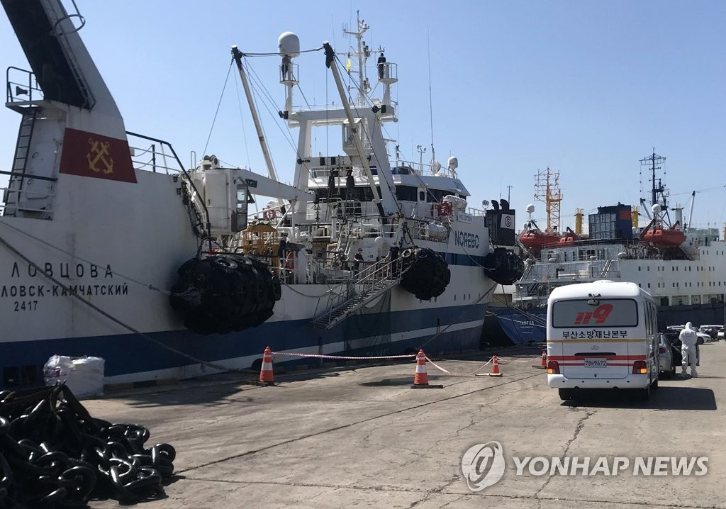 This photo, provided by fire service authorities in the southeastern port city of Busan on July 17, 2020, shows firefighters transferring Russian sailors infected with COVID-19 to a hospital for treatment. (PHOTO NOT FOR SALE) (Yonhap)