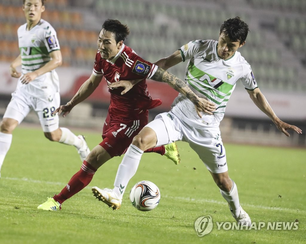Han Kyo-won of Jeonbuk Hyundai Motors (R) and Kim Byung-oh of Busan IPark battles for the ball during their quarterfinals match at the Korea Football Association Cup at Busan Gudeok Stadium in Busan, 450 kilometers southeast of Seoul, on July 29, 2020. (Yonhap)