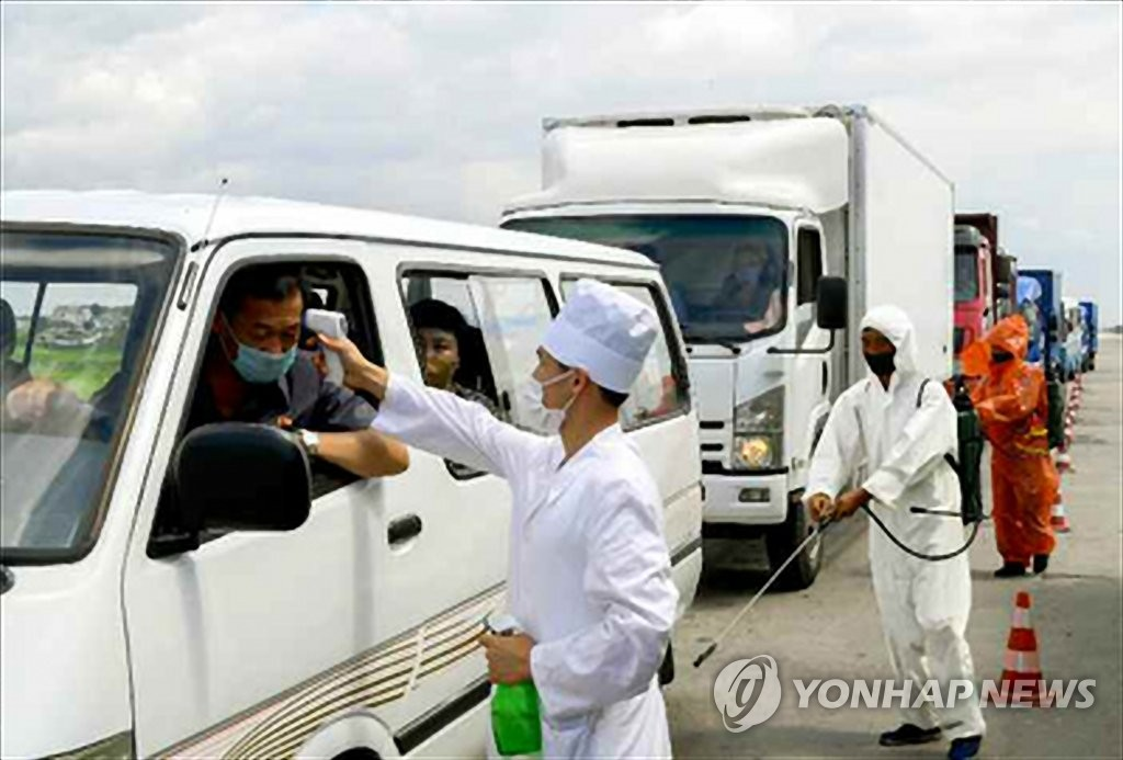 A North Korean antivirus worker takes the temperature of a car passenger by using a non-contact thermometer in this photo released by the Rodong Sinmun, the official newspaper of the North's ruling party, on July 31, 2020. (For Use Only in the Republic of Korea. No Redistribution) (Yonhap)