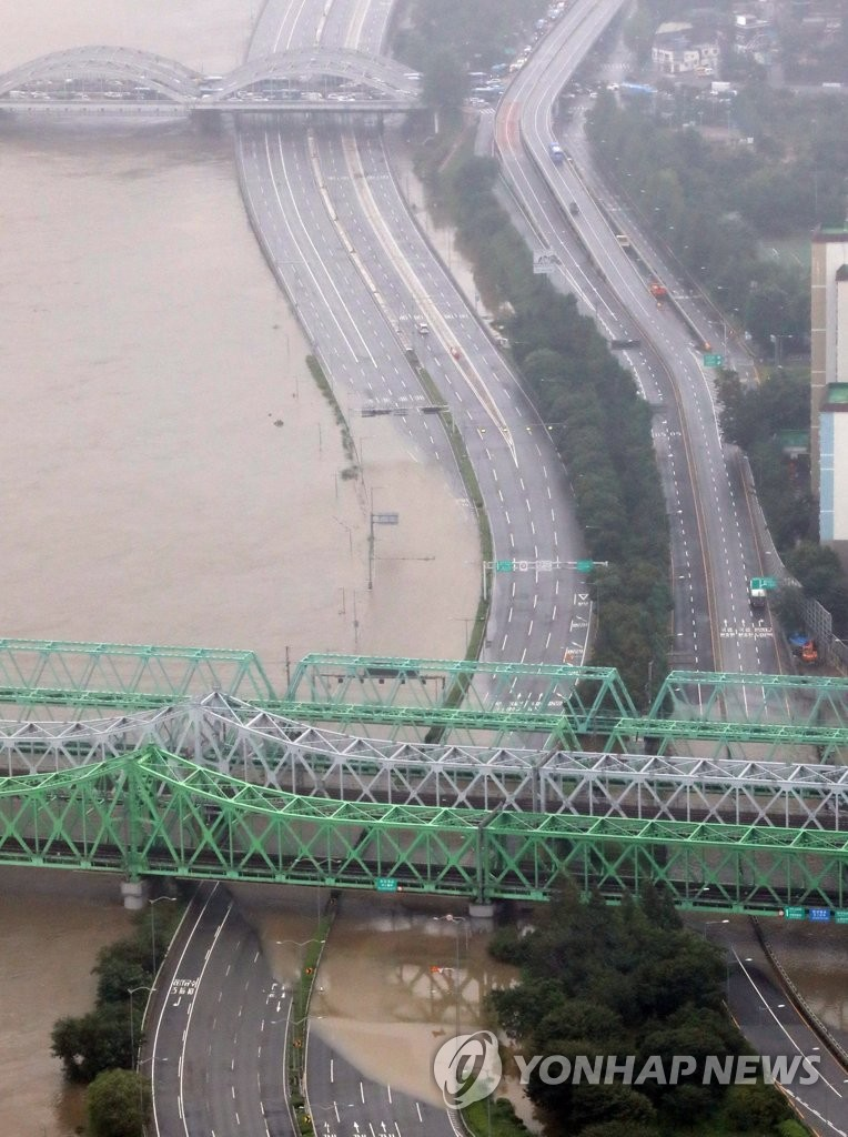 Roads along the Han River in Seoul are empty on Aug. 6, 2020, as the river was swollen amid torrential rain. (Yonhap)