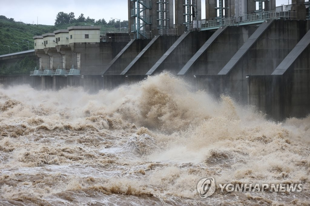 Water gushes out of the floodgates of the Gunnam Dam on the Imjin River that runs across the inter-Korean border in the South Korean border town of Yeoncheon, north of Seoul, on Aug. 6, 2020. The state-run Korea Water Resources Corp. opened all of the dam's 13 floodgates to lower the water level after the region received heavy rain. The dam, opened in 2010, was designed to deal with flash floods from North Korea. (Yonhap)