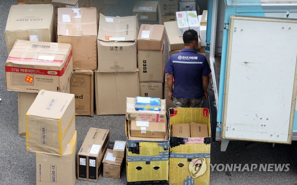A delivery worker sorts through items that need to be delivered at a logistics center in Seoul on Aug. 13, 2020, a day before the industry went on a one-day special holiday. (Yonhap)