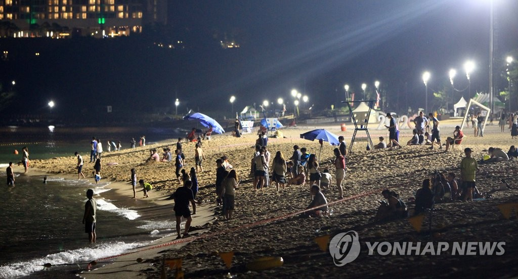 People relax at a beach in the eastern coastal city of Sokcho, Gangwon Province, on Aug. 13, 2020. (Yonhap)
