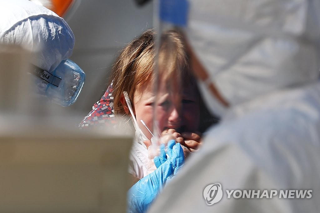 A child waits to receive a new coronavirus test at a makeshift clinic in central Seoul on Aug. 19, 2020. (Yonhap)