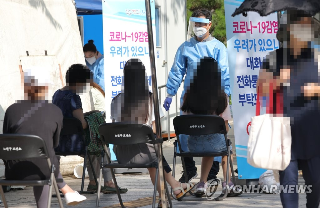 People wait to receive coronavirus tests at a virus screening clinic in Seoul on Aug. 25, 2020. (Yonhap)