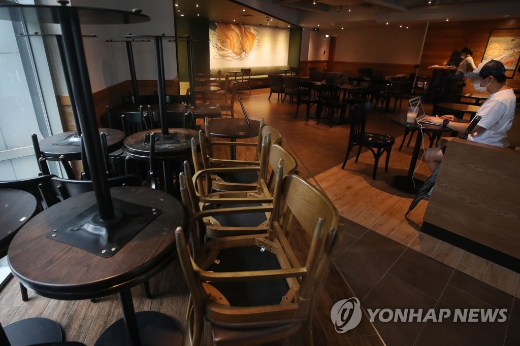 Tables and chairs are moved to a corner of a large cafe in downtown Seoul in preparation for the government's heightened social distancing rules that go into effect on Aug. 30, 2020. (Yonhap)