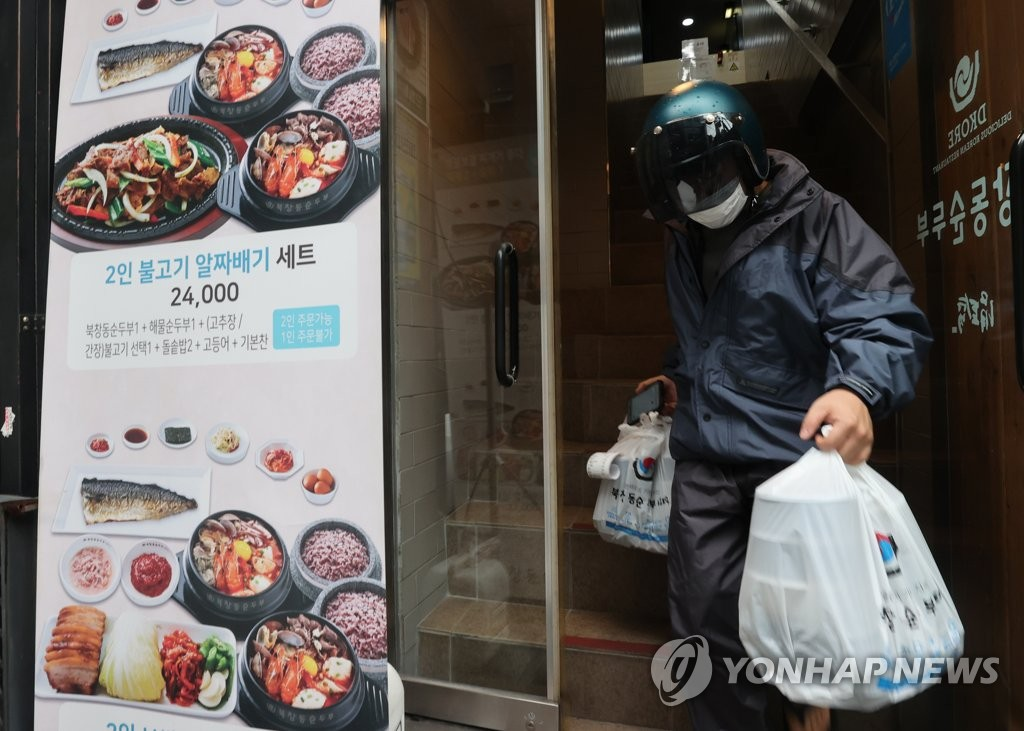A delivery man takes out meals from a resturant located in central Seoul on Sept. 2, 2020. (Yonhap)