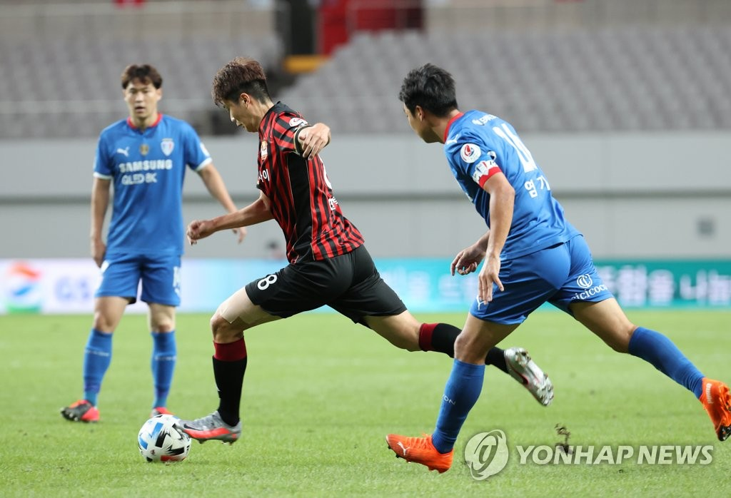Ki Sung-yueng of FC Seoul (C) dribbles past Yeom Ki-hun of Suwon Samsung Bluewings (R) during the clubs' K League 1 match at Seoul World Cup Stadium in Seoul on Sept. 13, 2020. (Yonhap)