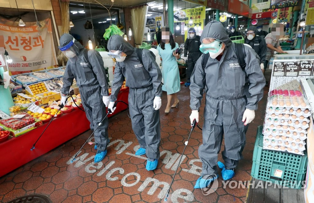 Sanitary workers disinfect the floor of a traditional market in Incheon, west of Seoul, on Sept. 15, 2020. (Yonhap)