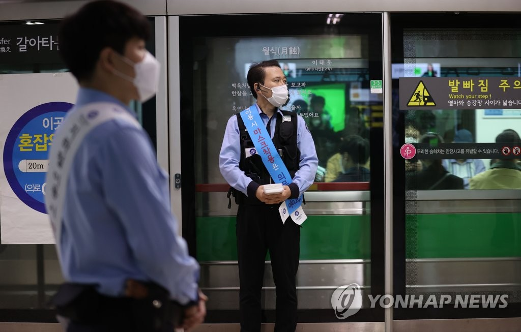 Workers urge commuters to wear protective masks at a subway station in southern Seoul on Oct. 13, 2020. (Yonhap)