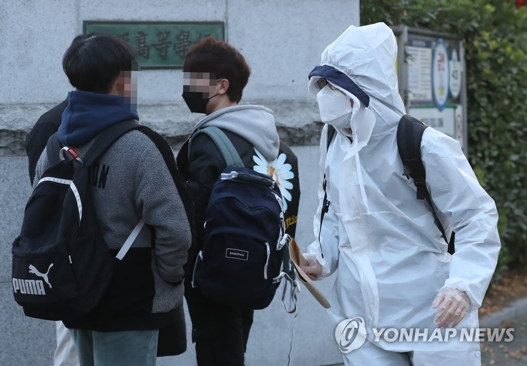 A student taking the College Scholastic Ability Test arrives in a protective suit at a high school in Incheon, west of Seoul, on Dec. 3, 2020. (Yonhap)