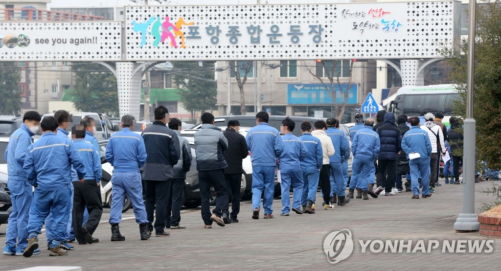Workers at the Pohang steel industrial complex, 374 kilometers southeast of Seoul, line up in front of a screening center set up at the Pohang Sports Complex to take coronavirus tests on Dec. 11, 2020. (Yonhap)