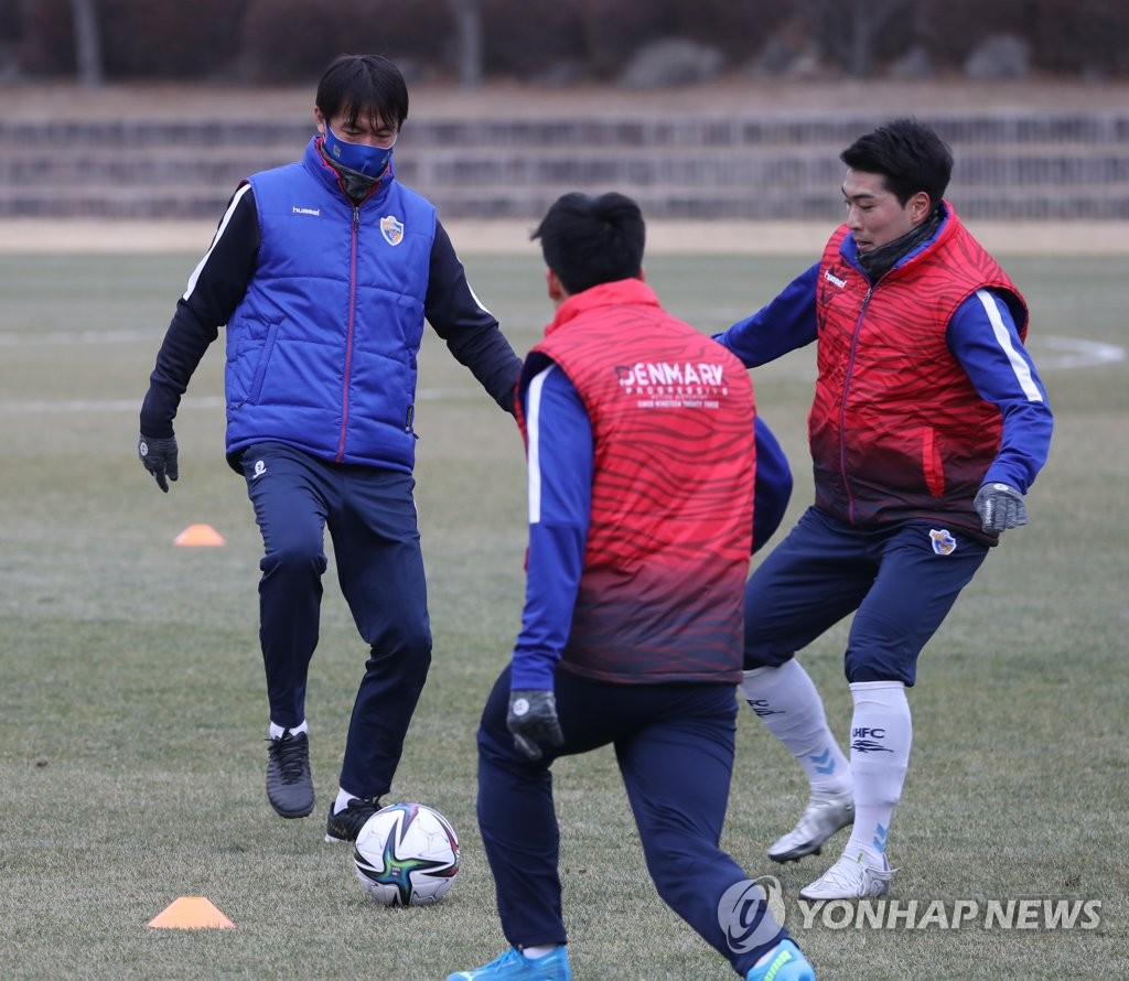 Hong Myung-bo (L), head coach of Ulsan Hyundai FC, controls the ball during a practice session at Gangdong Football Stadium in Ulsan, 415 kilometers southeast of Seoul, on Jan. 11, 2021. (Yonhap)