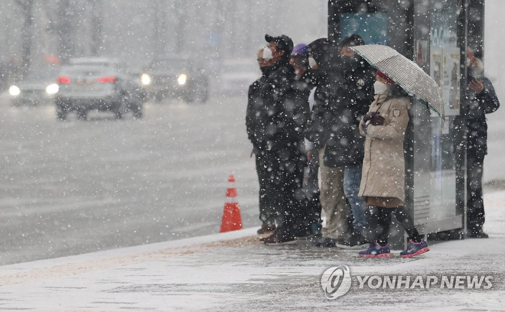 People wait in the snow for buses near Gwanghwamun Square in central Seoul on Jan. 12, 2021. (Yonhap)