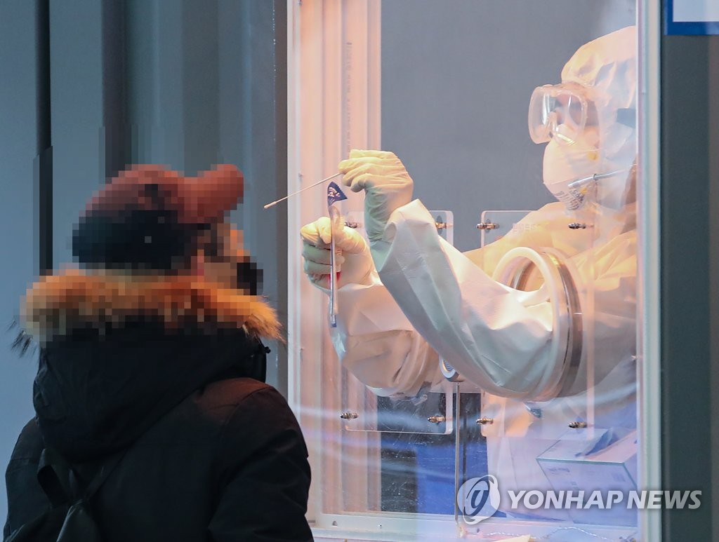 A visitor receives a COVID-19 test at a makeshift clinic in Seoul on Jan. 14, 2021. (Yonhap)