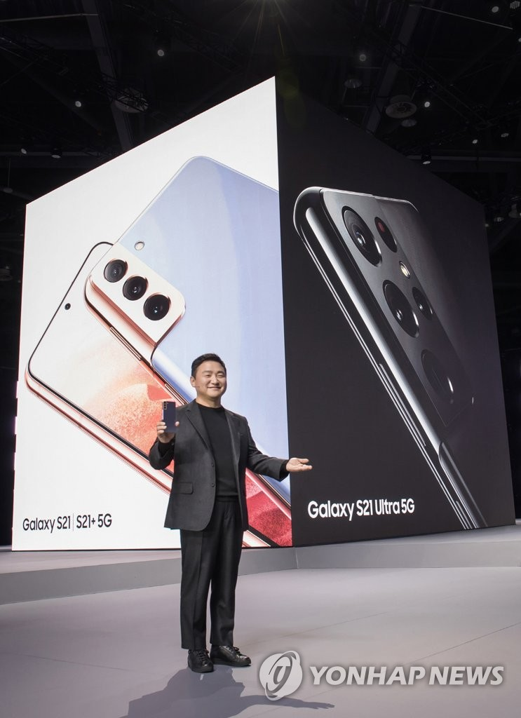 This photo provided by Samsung Electronics Co. on Jan. 15, 2021, shows Roh Tae-moon, who heads Samsung's mobile business, holding the Galaxy S21 smartphone at the Galaxy Unpacked 2021 online event. (PHOTO NOT FOR SALE) (Yonhap)