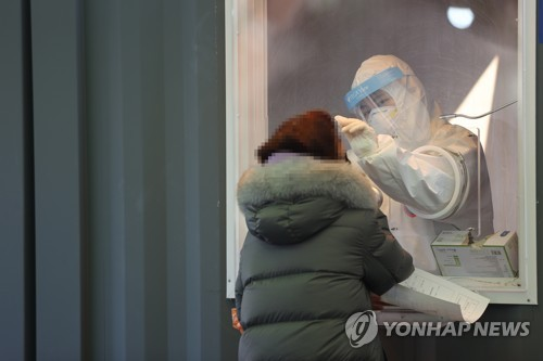 A medical worker collects a specimen from a woman at a temporary COVID-19 screening station set up in front of Seoul Station on Jan. 16, 2020. (Yonhap)