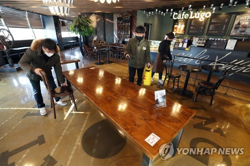 Employees of a cafe in the southeastern city of Daegu set up tables on Jan. 17, 2021, one day before the government eased social distancing regulations on coffee shops. (Yonhap)