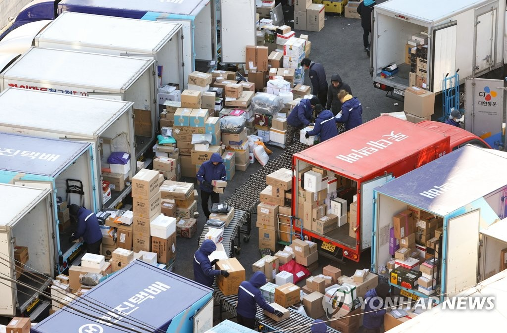 Workers sort parcels at a distribution center in Seoul on Jan. 19, 2021. (Yonhap)