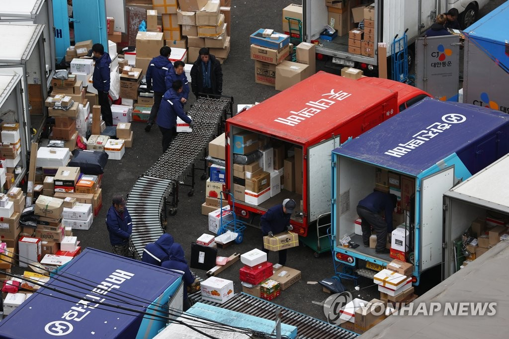In this file photo, delivery workers sort parcels at a distribution center in Seoul on Jan. 21, 2021. (Yonhap)