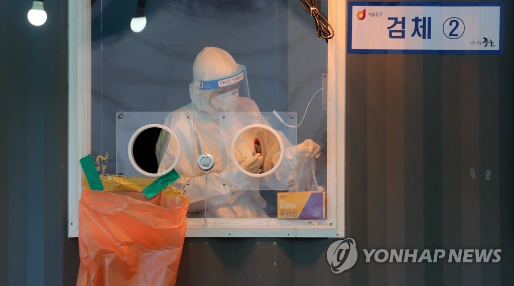 A medical worker gets ready for COVID-19 testing at a temporary screening station in front of Seoul Station on Feb. 18, 2021. (Yonhap)