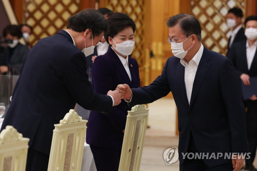 President Moon Jae-in (R) bumps fists with ruling Democratic Party leader Lee Nak-yon during a meeting at Cheong Wa Dae in Seoul on Feb. 19, 2021. (Yonhap)