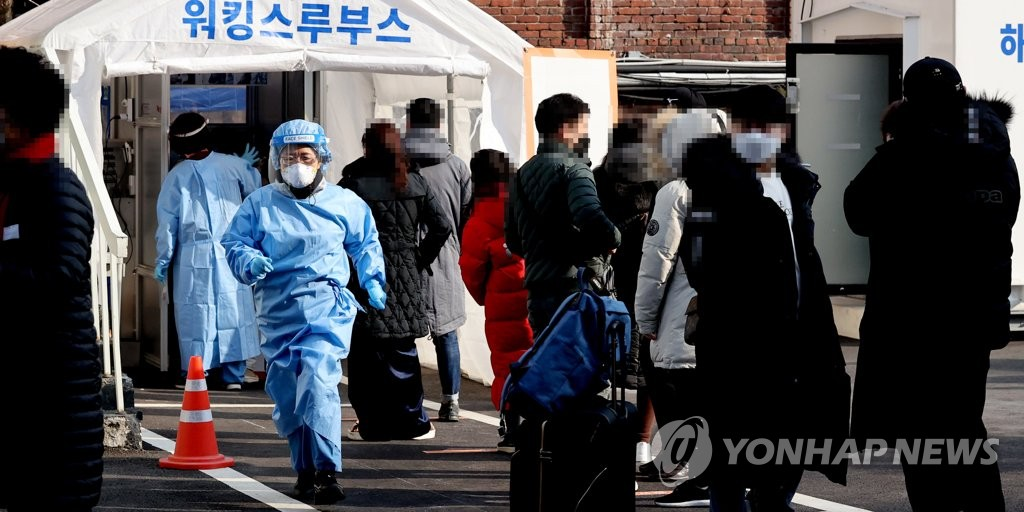 Visitors wait to get tested for the new coronavirus at a makeshift clinic in Seoul on Feb. 21, 2021. (Yonhap)