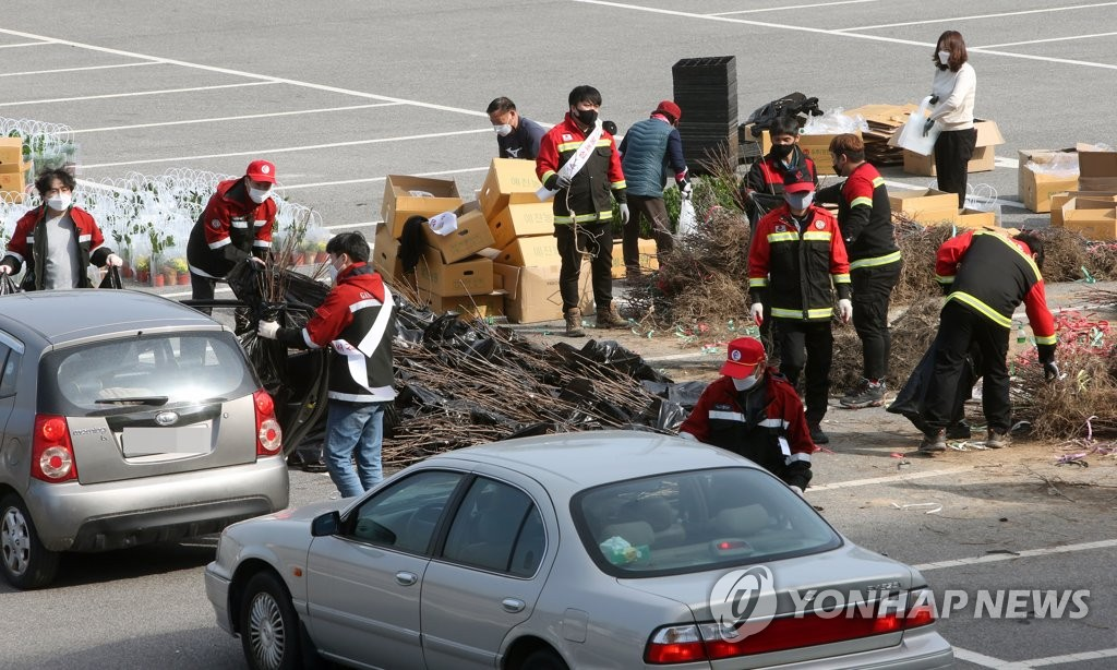 This photo taken on March 26, 2021, shows Gangneung City government officials delivering seedlings to citizens in their cars in a drive-thru event ahead of Arbor Day on April 5. (Yonhap)