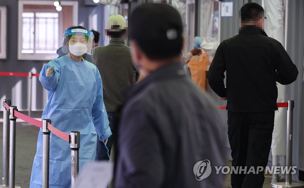 A medical worker guides visitors at a makeshift COVID-19 test center in central Seoul on April 11, 2021. (Yonhap)