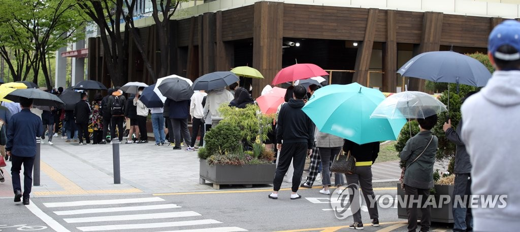 People stand in line to get COVID-19 tests at a Seoul clinic on April 12, 2021. (Yonhap)