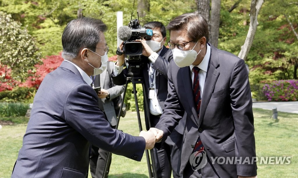 President Moon Jae-in (L) bumps fists with Busan Mayor Park Heong-joon at Cheong Wa Dae in Seoul on April 21, 2021. (Yonhap)