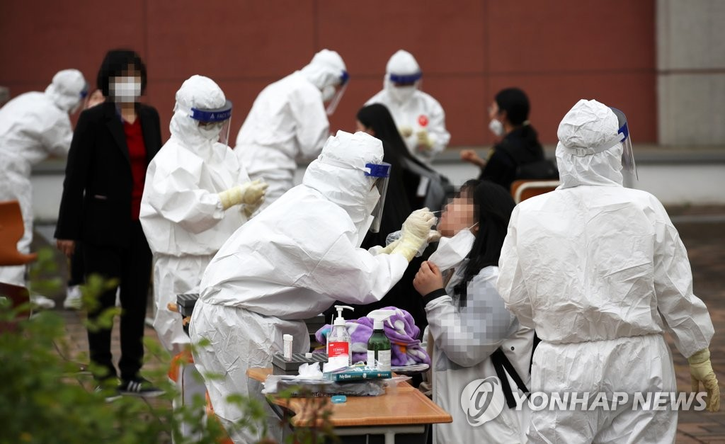 This photo, taken April 22, 2021, shows health workers clad in protective suits collecting samples from students for COVID-19 tests at a makeshift virus testing clinic in Gwangju, 329 kilometers south of Seoul. (Yonhap)