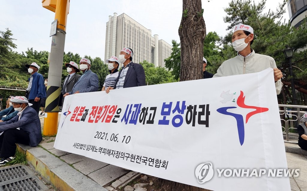 In this file photo, members of a civic group supporting victims of wartime forced labor in Japan rally in front of the Seoul Central District Court on June 14, 2021, to denounce the court's dismissal on June 7 of a damages suit launched by 85 South Korean victims of wartime forced labor in Japan and their families against 16 Japanese companies. (Yonhap)