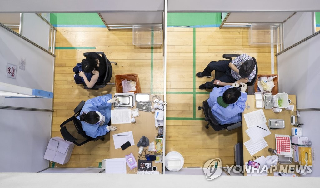 Medical workers administer COVID-19 vaccines at a makeshift vaccination center in northern Seoul on June 16, 2021. (Yonhap)