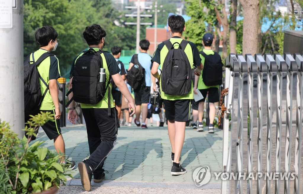 Students arrive at a middle school in Seoul on June 21, 2021, as health authorities are set to apply eased social distancing rules next month.