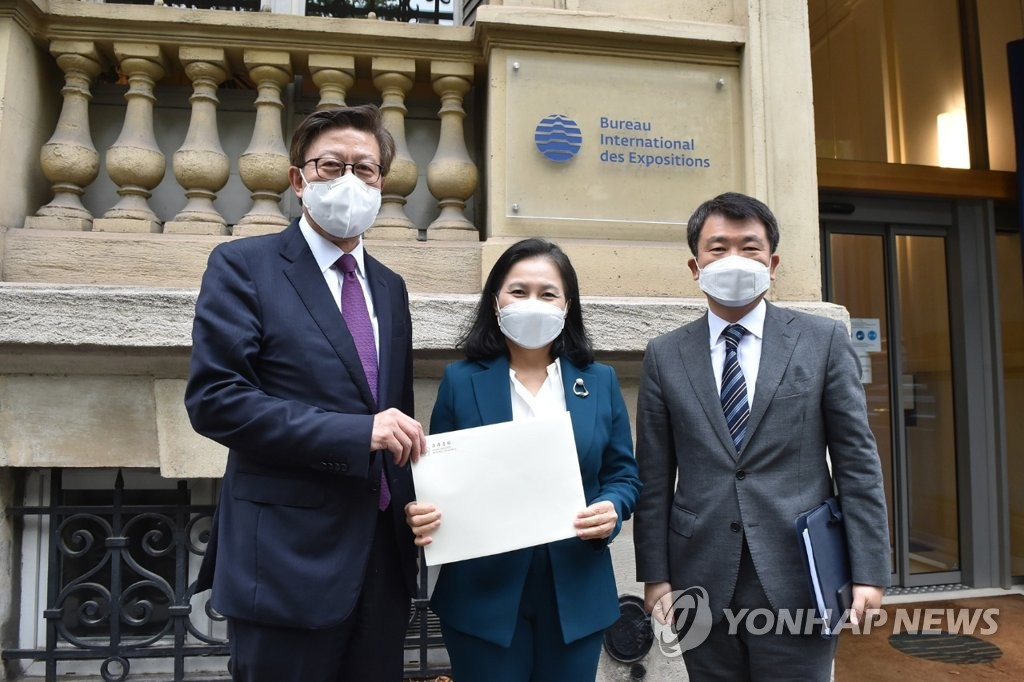 Trade Minister Yoo Myung-hee (C) poses for a photo in front of the main headquarters of the Bureau of International des Expositions (BIE) in Paris in this file photo provided by the Busan Metropolitan City on June 23, 2021. (PHOTO NOT FOR SALE) (Yonhap)