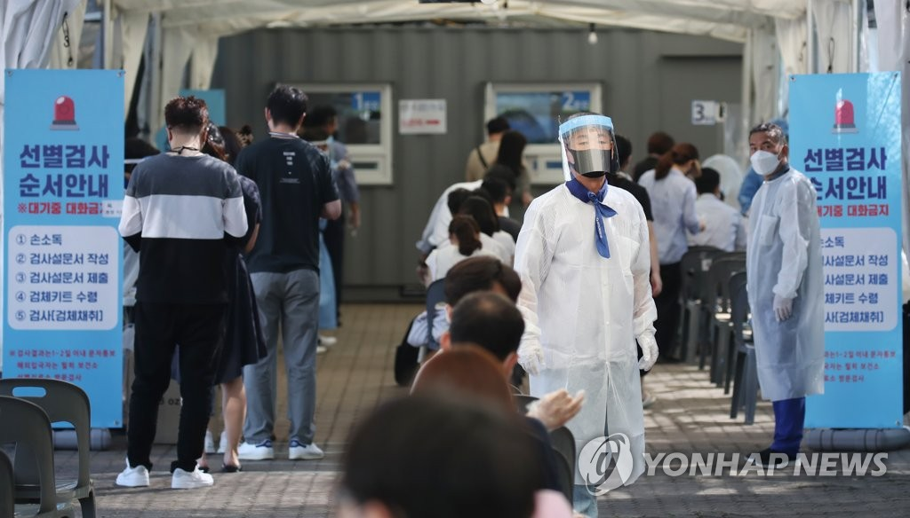 A health worker in a protective suit guides citizens at a makeshift virus testing clinic in Seoul on July 28, 2021. (Yonhap)