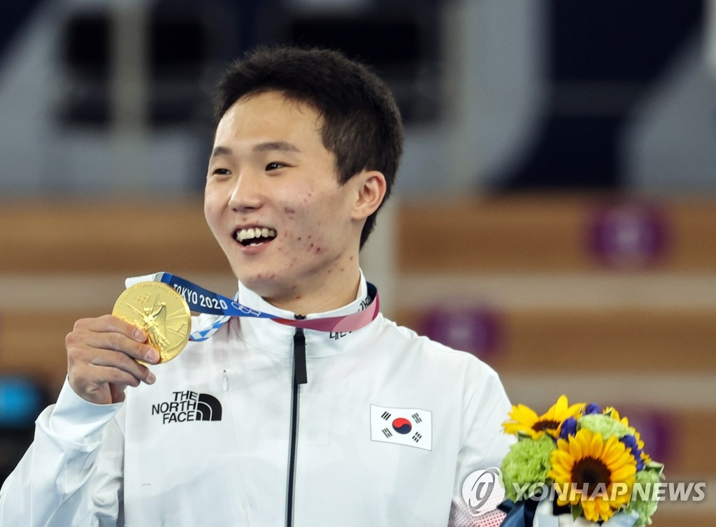 South Korean gymnast Shin Jea-hwan holds up his gold medal in the men's vault at the Tokyo Olympics at Ariake Gymnastics Centre in Tokyo on Aug. 2, 2021. (Yonhap)
