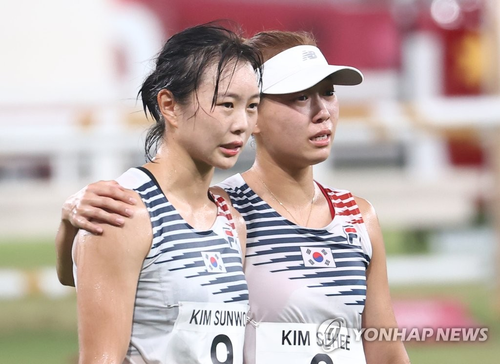 Kim Sun-woo (L) and Kim Se-hee of South Korea put their arms around each other's shoulders after completing the laser run portion of modern pentathlon at the Tokyo Olympics at Tokyo Stadium in Tokyo on Aug. 6, 2021. (Yonhap)