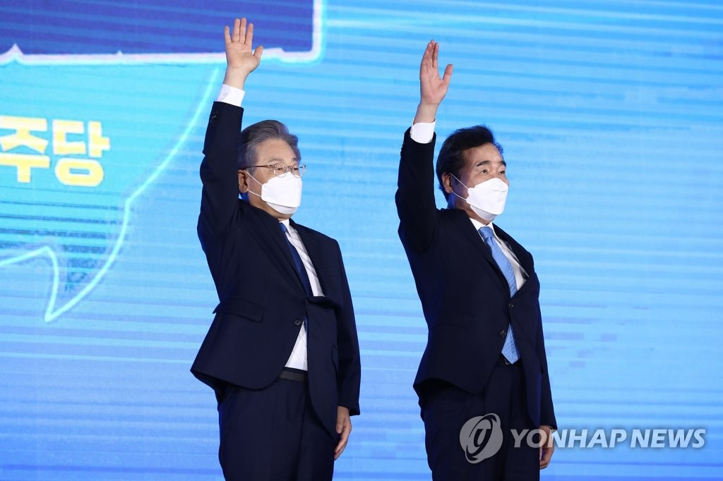 Gyeonggi Gov. Lee Jae-myung (L) and former Prime Minister Lee Nak-yon pose for photos after the governor was chosen as the Democratic Party's presidential nominee at a handball stadium in eastern Seoul on Oct. 10, 2021. (Pool photo) (Yonhap)
